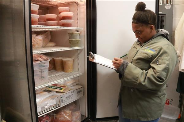 Food Service student taking inventory in freezer and smiling