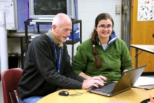 Teacher and student using laptop and smiling