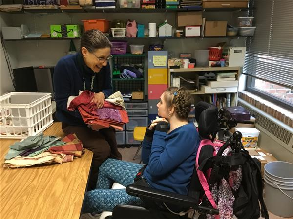 student and occupational therapist collaborating on quilting project