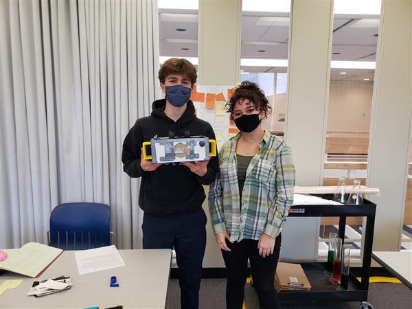 two engineering students display their pinhole camera