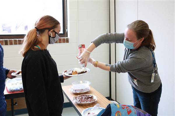 staff with mask putting whip cream on a student's pie
