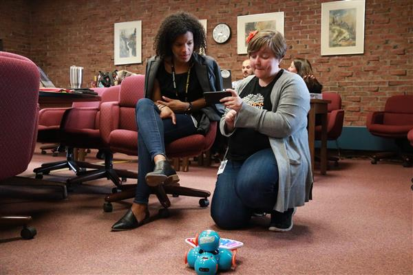 two educators experimenting with robotic teaching tool