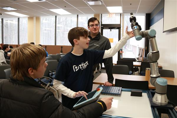 p-tech student learning how to program a robotic arm