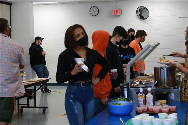 regional alternative school student wearing mask posing and smiling while getting Thanksgiving food