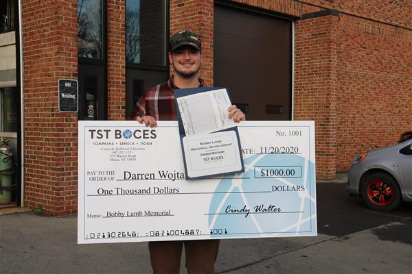 Darren holding large check